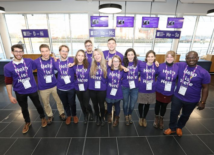 A group of people stand in a line wearing purple t-shirts saying 'Help is Here'