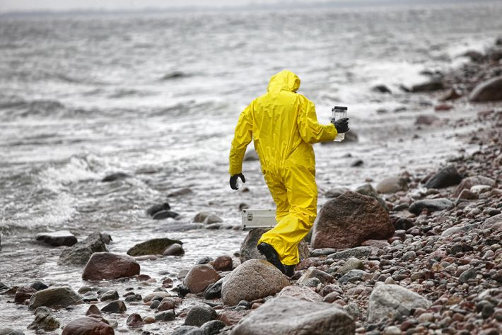 A person in yellow, waterproof overalls carrying a plastic container on a pebble beach