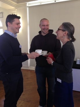 Happy facilitators sharing a tea and a biscuit before the start of the event